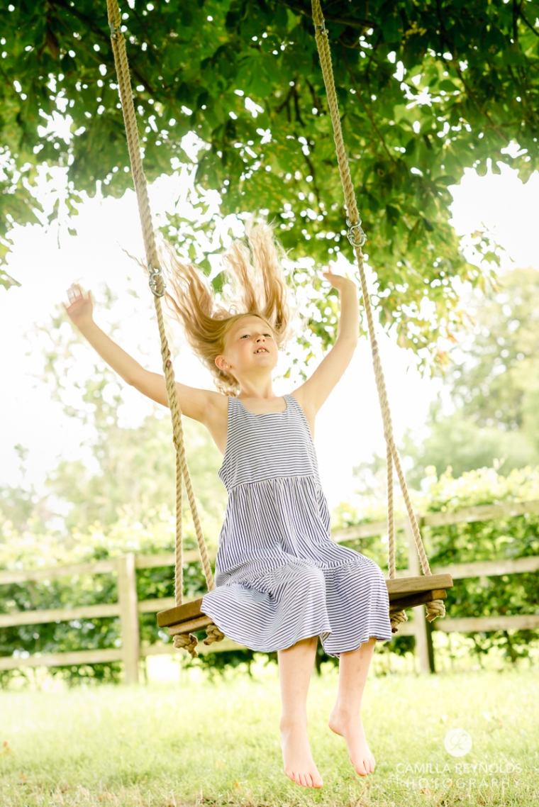 fun relaxed family photo session Cotswolds girl swing