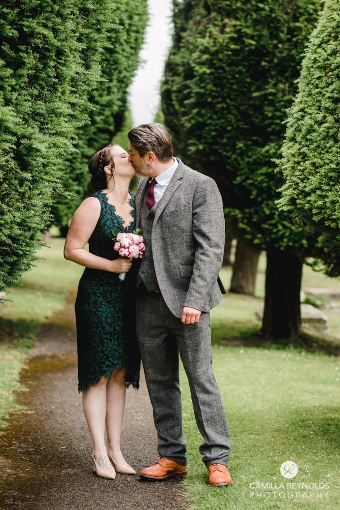 bride and groom kissing among trees wedding photos