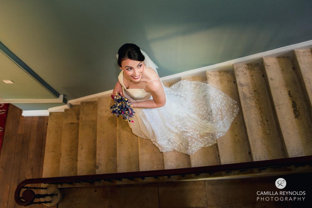 bride walking down staircase manor house wedding Cheltenham Gloucestershire