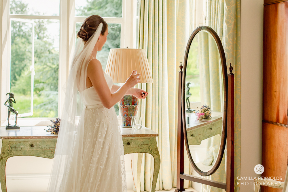 bride putting perfume on romantic wedding photography cotswolds
