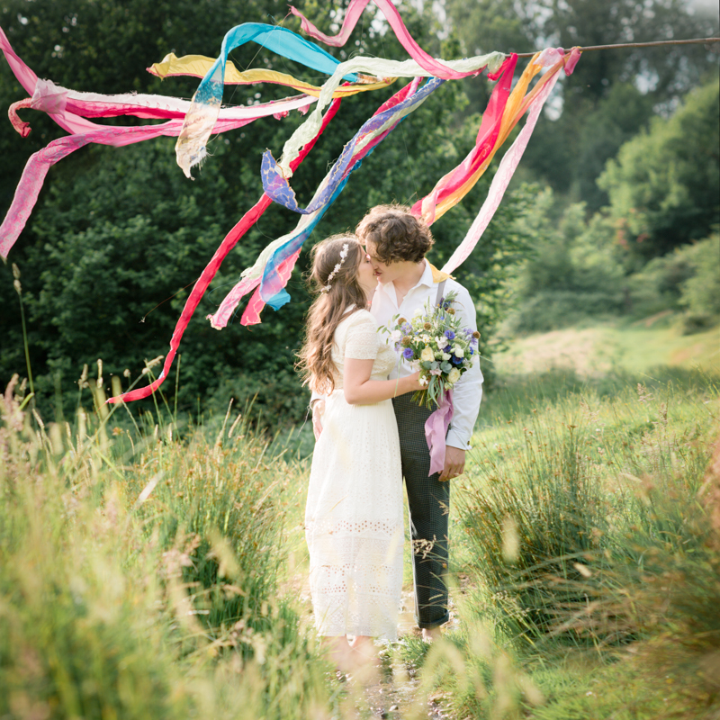bride and groom in a field alternative colourful wedding