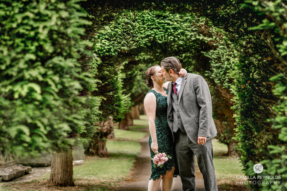 bride and groom kissing churchyard st marys church wedding  gloucestershire