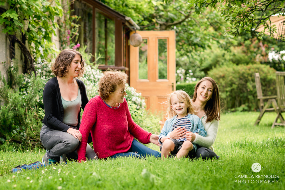smiling natural  family portrait in the garden gloucestershire