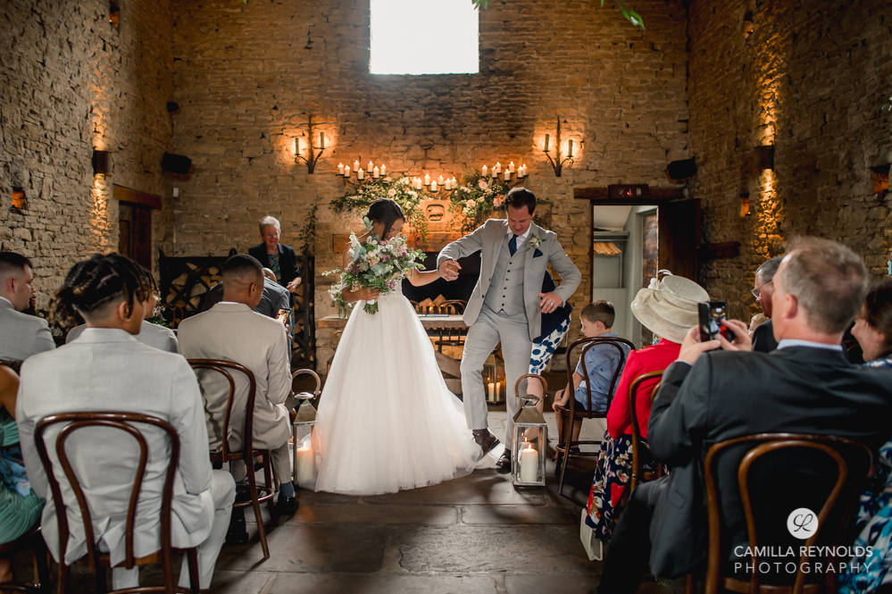 groom stepping on dress fun natural wedding photography cotswolds