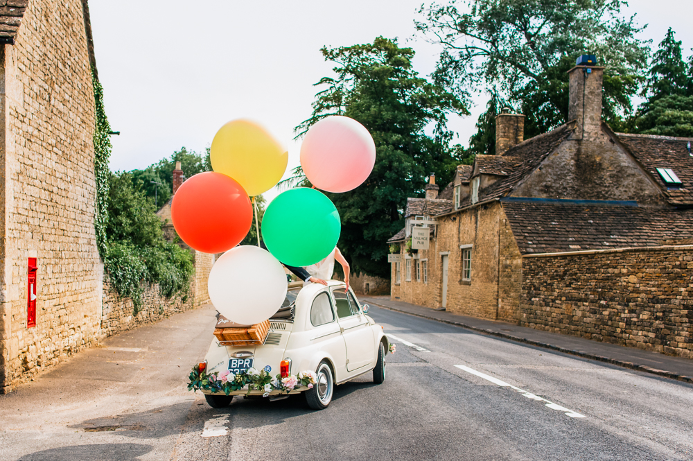 car with vibrant balloons fun natural wedding photography barnsley cotswolds uk
