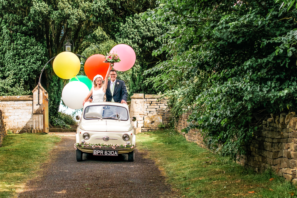 bride and groom car with colourful balloons fun wedding photography uk