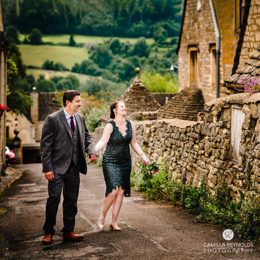 wedding couple walking in beautiful cotswold village countryside views