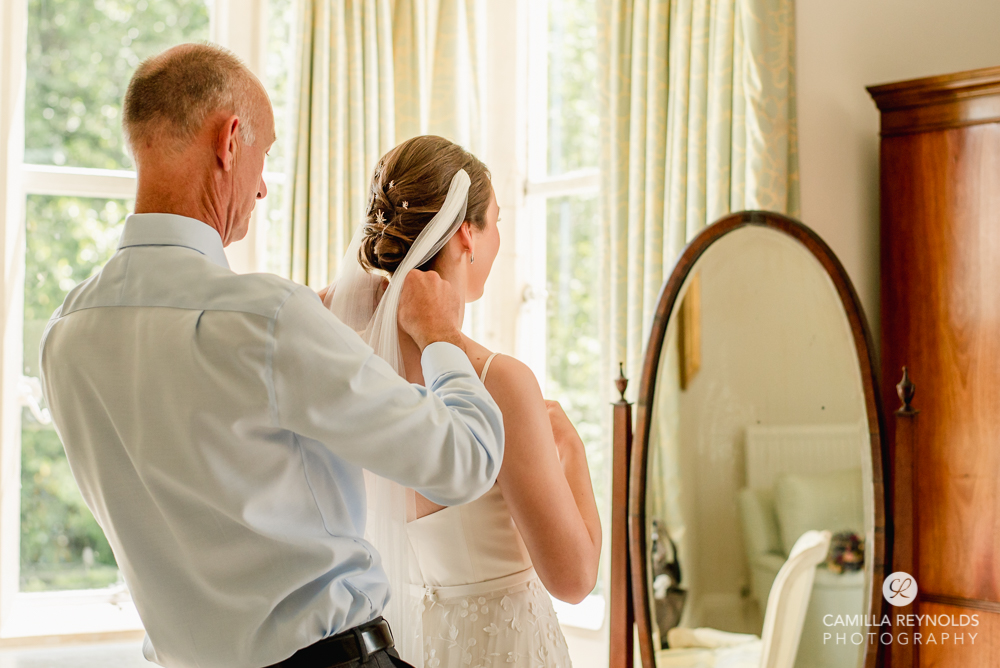 father of the bride putting a necklace on bride cotswold wedding