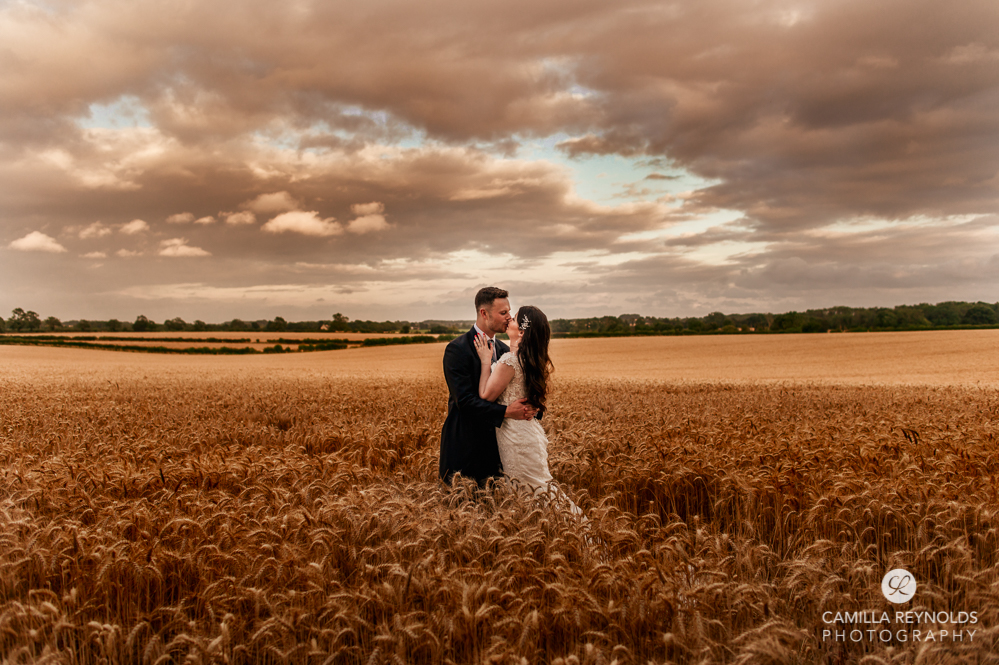 bride and groom kissing in field romantic wedding photography uk