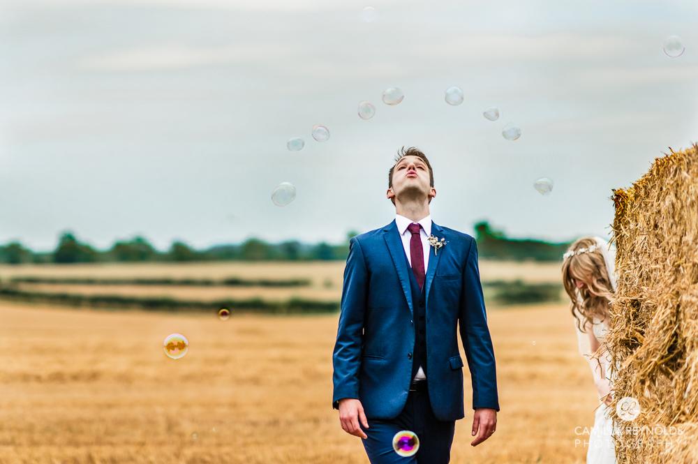 groom blowing bubbles fun wedding photography uk
