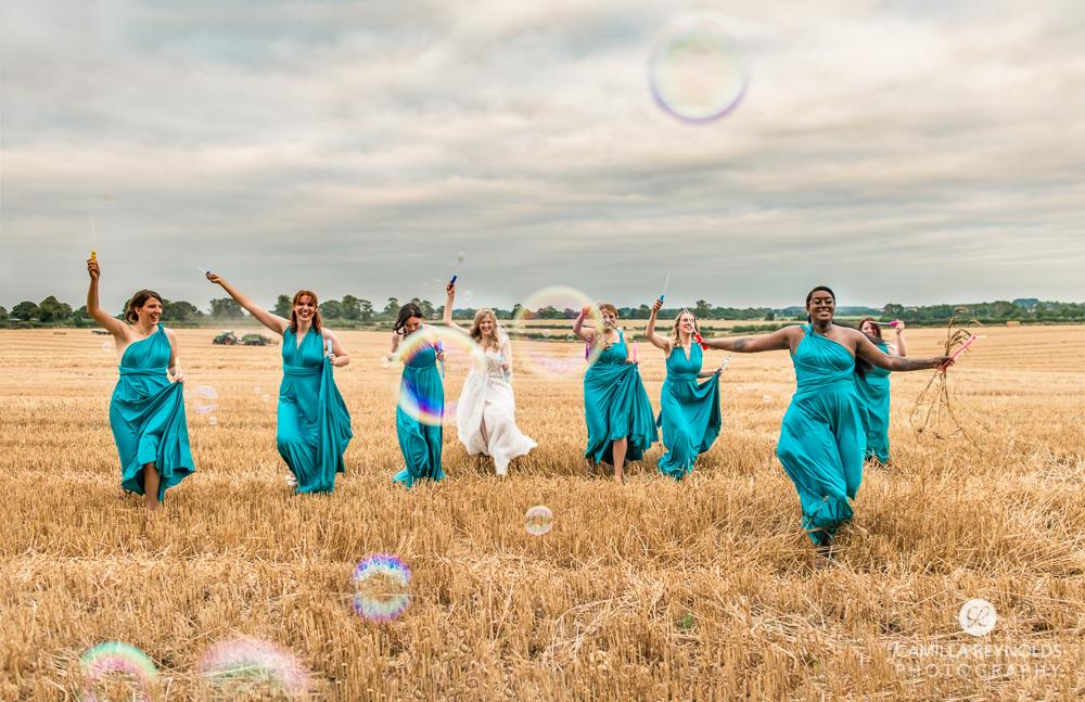 bride and bridesmaid running with bubbles fun natural wedding photography uk