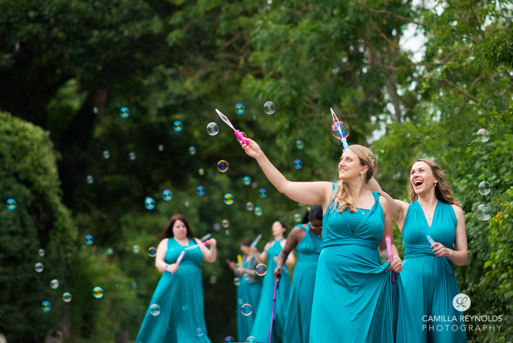 bridesmaids in blue dresses with bubbles natural wedding photography uk