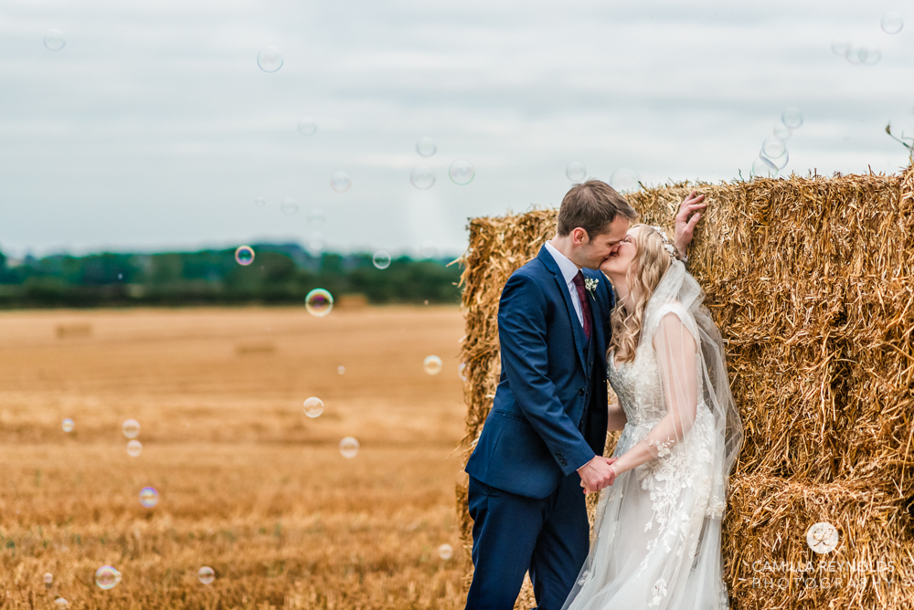 bride and groom kissing by hay bale with bubbles cotswold  wedding photo