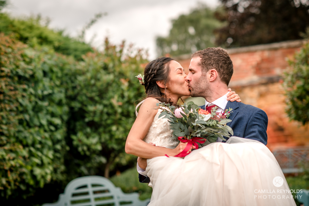 bride and groom kissing in garden wedding Cotswolds