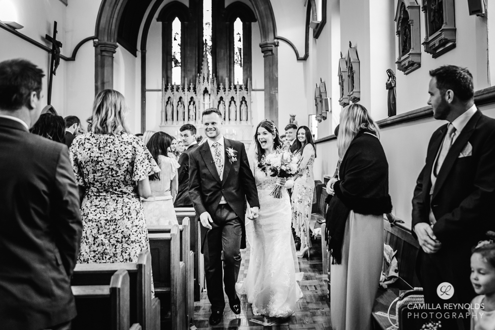 bride and groom walking cotswold wedding st peters church cirencester