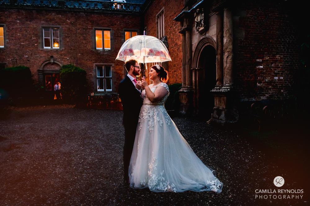 bride and groom with umbrella rainy wedding photography Grafton manor uk