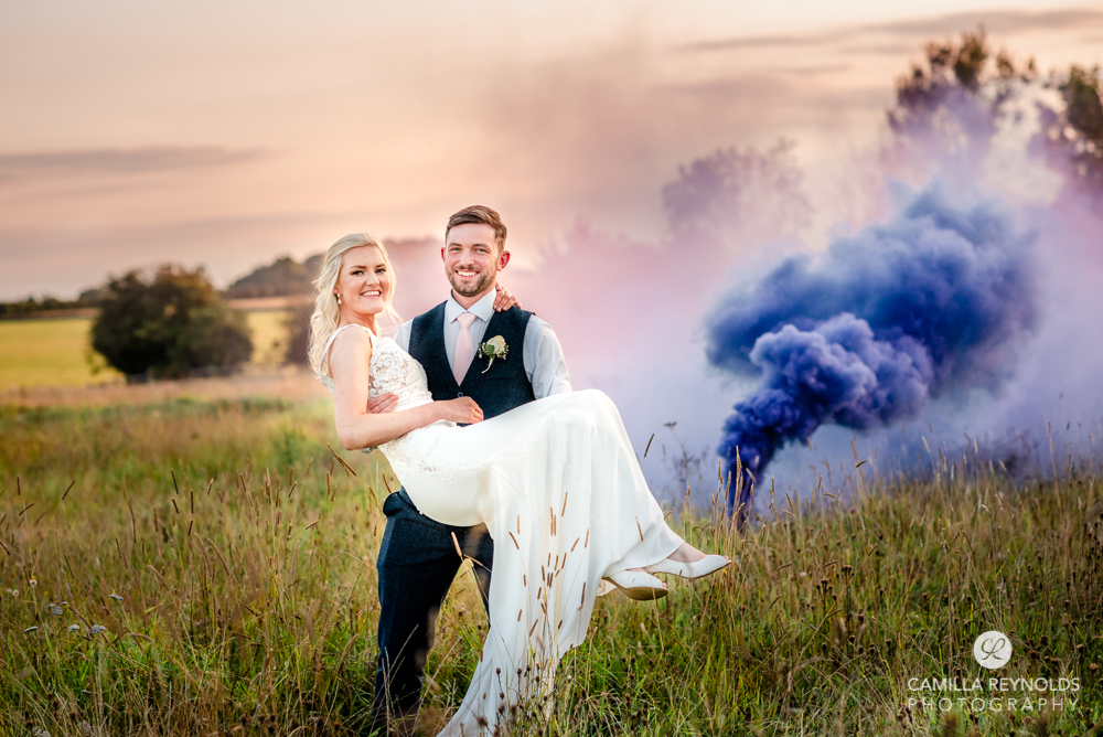 bride and groom in a field smoke flare vibrant wedding photography uk