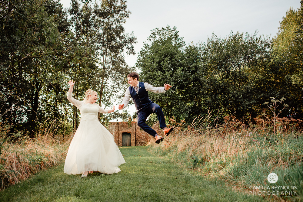 bride and groom jumping fun wedding photography cotswolds