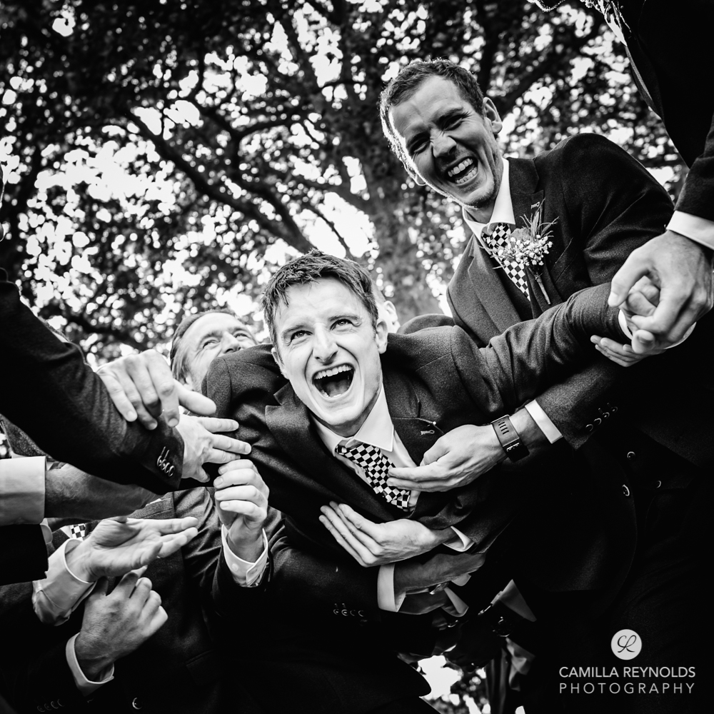 groom thrown in the air natural wedding photography Gloucestershire uk