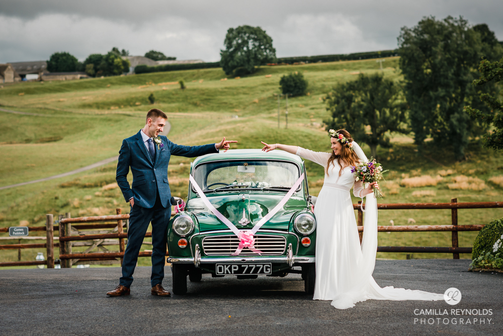 bride and groom with morris minor car wedding photography gloucestershire kingscote barn