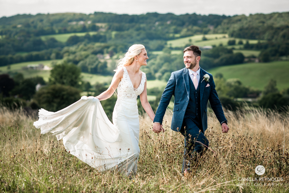 bride and groom walking in the countryside cotswolds wedding
