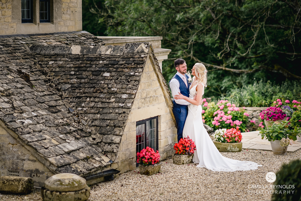 bride and groom cotswold house stone wall Gloucestershire uk
