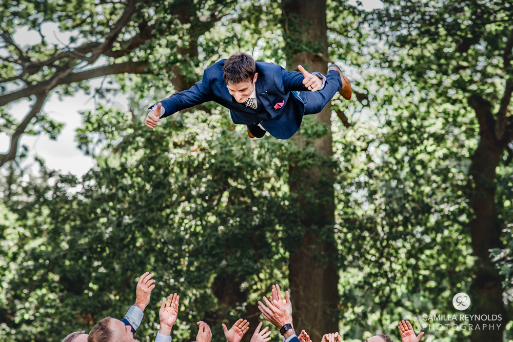 groom thrown in the air by groomsmen fun wedding photography cotswolds