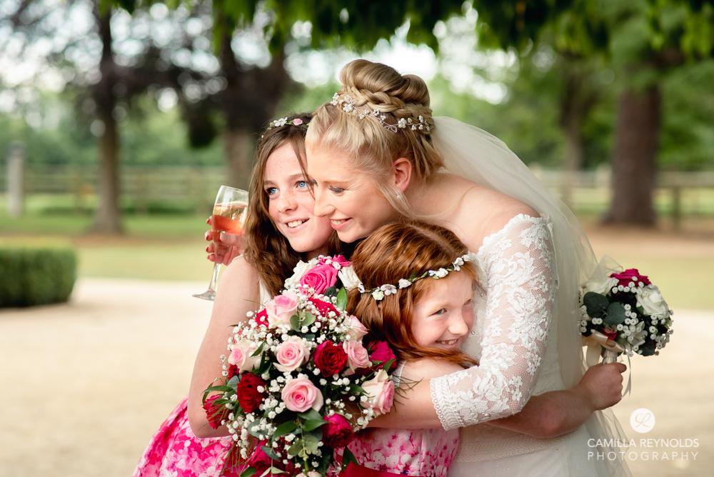 bride hugging bridesmaids natural wedding photography cotswolds uk
