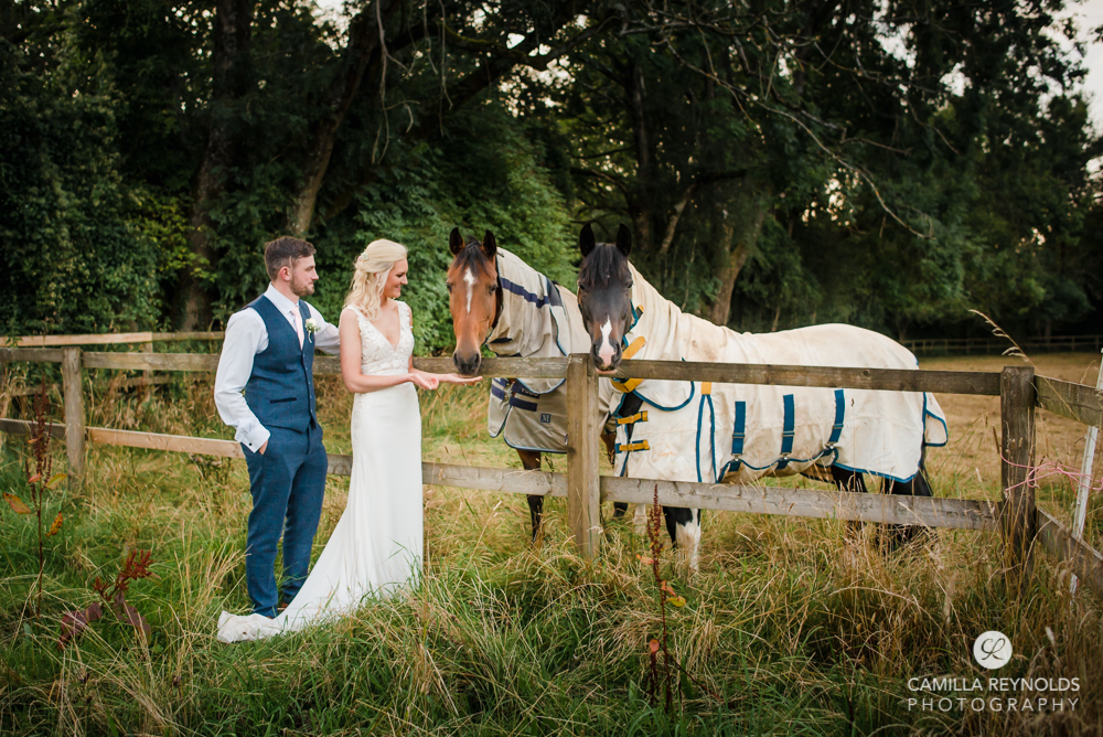 bride and groom with horses Cotswold wedding Gloucestershire uk